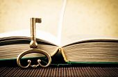 Old metal key and open book - old style photo
