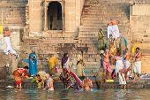 Pilgrims Bathing In The Ganges River In Varanasi, India