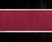 Dark scarlet rustic canvas banner textured with dark wood background