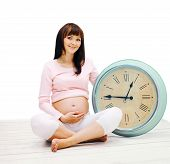 Happy Pregnant Woman Sitting On The Floor With A Big Clock On A White Background