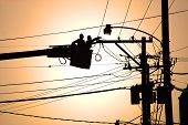 stock photo of utility pole  - Utility crew in a boom bucket working on highlines - JPG
