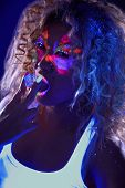 picture of uv-light  - Portrait of beautiful curly girl posing in ultraviolet light - JPG