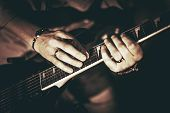stock photo of brownie  - Rockman Playing Electric Guitar Closeup Photography. Hands on Guitar. Elegant Browny Color Grading.
