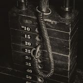 Antique tones on an old rusty weight stack in a gym.