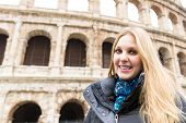 Happy blonde tourist at the Colosseum in Rome, Italy.