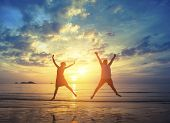 Honeymoon. Young couple jumping on the sea beach during amazing sunset. Vacation and Nature.