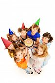 Group of happy kids celebrating birthday with a cake. Isolated over white.
