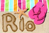 Rio. Overhead view ot the word RIO written on beach sand with a colorful striped towel, pink thongs and a starfish conceptual of a summer vacation and travel in Rio de Janiero, Brazil