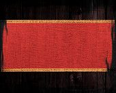 Crimson red rustic canvas banner textured with dark wood background