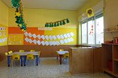 Preschool Classroom With Chairs And Table With Drawings Of Children
