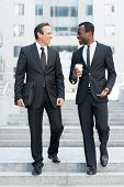 stock photo of staircases  - Full length of two cheerful business men talking while moving down by staircase - JPG