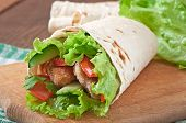 Fresh tortilla wraps with chicken nuggets and vegetables on plate