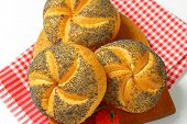 detail of fresh poppy seed buns on wooden cutting board and checkered dishtowel