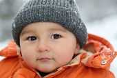Baby Boy With Snow And Cap In Winter Looking Into Camera