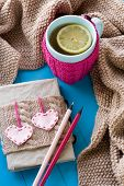 stock photo of blanket snow  - A cup of tea in sweater with lemon old notebook with hearts of felt beige knitted blanket and spokes lie on blue background - JPG