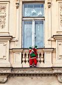 Santa Claus Is Climbing Up A Facade