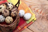 Quail Eggs In A Wicker Basket On A Wooden Background With Napkin
