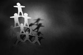 image of human pyramid  - Human team pyramid on dark background - JPG