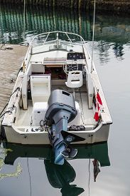 picture of outboard  - A small white boat at a dock with a black outboard motor and a Canadian flag - JPG