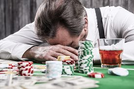 picture of suspenders  - Depressed senior man in shirt and suspenders leaning his head at the poker table with money and gambling chips laying all around him - JPG