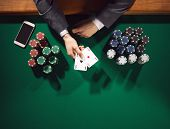 foto of poker hand  - Elegant male poker player with smartphone holding two aces with stacks of chips all around hands detail top view - JPG