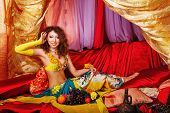 stock photo of harem  - Young oriental beauty sitting in the tent and straightens her hair - JPG