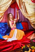 stock photo of harem  - Sexy oriental beauty in a tent and holding a multicolored beads - JPG