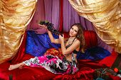 foto of harem  - Sexy oriental beauty sitting in a tent and holding a grape - JPG