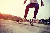 stock photo of skateboard  - young woman skateboarder practice skateboarding trick ollie outdoor - JPG