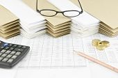 stock photo of spectacles  - Brown pencil and pile of gold coins with calculator on finance account have spectacles on pile of paperwork with envelope as background - JPG