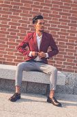 picture of blazer  - Young handsome Asian model dressed in red blazer sitting on a marble bench in the city streets - JPG