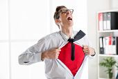 stock photo of angry man  - Angry businessman ripping open his shirt and exposing a Superhero red costume underneath - JPG