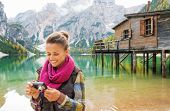 stock photo of pier a lake  - A smiling brunette wearing outdoor gear looks at the photo she has taken on her digital camera - JPG