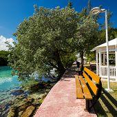 stock photo of pews  - Wooden bench in park near caribbean lagoon - JPG
