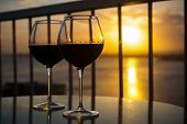 picture of caribbean  - Two red wine glasses in front of the setting sun - JPG