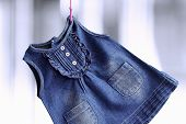 picture of habilis  - Fashion denim baby dress hanging on a hanger on a green background - JPG
