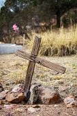 picture of crucifix  - Worn out wooden asymmetrical crucifix grave marker in desert - JPG