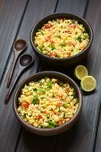 stock photo of sweet-corn  - Vegetarian couscous salad made with bell pepper tomato cucumber red onion and sweet corn kernels served in rustic bowls wooden spoons and lemon on the side - JPG