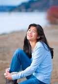 stock photo of biracial  - Young biracial teen girl in blue shirt and jeans sitting along rocky lake shore on bright overcast day outdoors - JPG