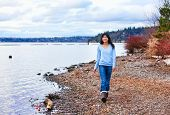 pic of shoreline  - Young biracial teen girl in blue shirt and jeans walking along rocky shoreline of lake in early spring or fall - JPG