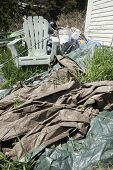 stock photo of junk-yard  - Garbage in back yard of house in grass - JPG