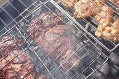 stock photo of charcoal  - grilled roast meats beef lamb fillet ribs on bbq grid over charcoal - JPG