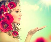 foto of hair blowing  - Beauty girl with red poppy flowers hairstyle and open hands - JPG