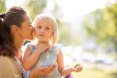 stock photo of i love you mom  - In a sunny city park a mother whispers loving words of encouragement into her blonde blue - JPG