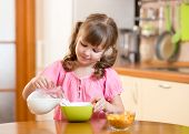 stock photo of healthy eating girl  - child girl eating healthy food at home in kitchen - JPG