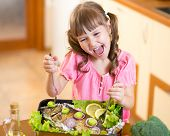 picture of healthy eating girl  - Funny child girl and grilled fish at kitchen - JPG
