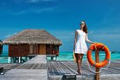 image of jetties  - Woman on a tropical beach jetty at Maldives - JPG