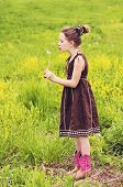 image of cowgirl  - Young girl in dress and cowgirl boots blows on a dandelion flower