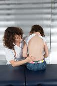 picture of scoliosis  - female doctor examines the back of young girl - JPG