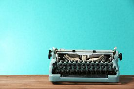 image of classic art  - Old retro typewriter on table on green background - JPG